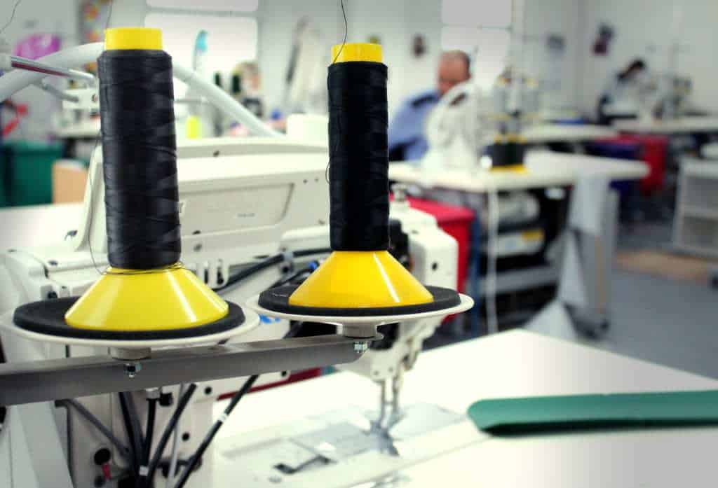 Spools with black thread on top of a sewing machine